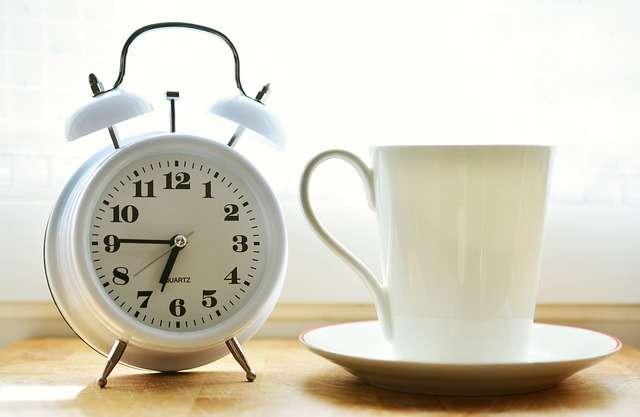 Снимката показва часовник и чаша кафе, които са част от сутрешната рутина на много хора.
