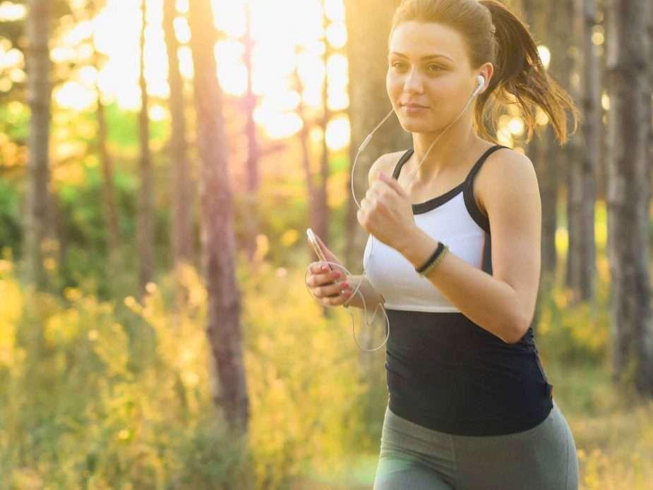 жена тича сред природата и слуша музика