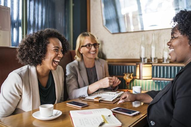 жени водят увлекателен разговор и се смеят по време на работна среща